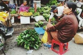 Teeblätter liegen auf der Erde. Die Frau kaut etwas, was ihren Mund rot färbt