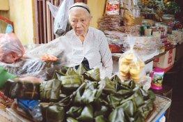 Alte Frau verkauft geleeartigen Kuchen in Bananenblättern