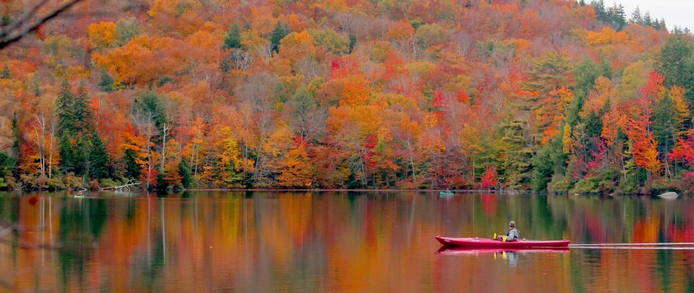 A kayaker on a fall day, surrounded by trees reflected in the lake.  One of  the four things we love about autumn from Game Changer Products LLC.
