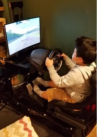 本物の自動車と同じようにハンドルとペダルでプレイするeモータースポーツ