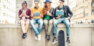 pubertät-fakten-blog vier teenager sitzen auf einer mauer und lesen