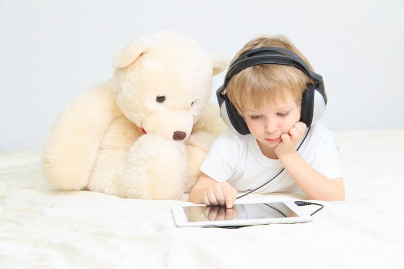 kleiner junge mit teddybär am tablet schaut einen film