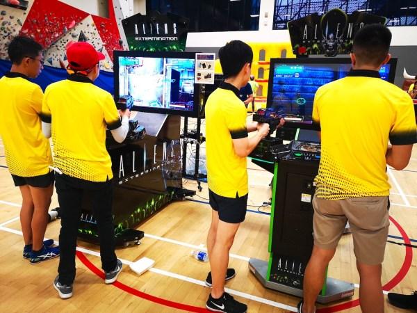 People playing shooting arcade machine