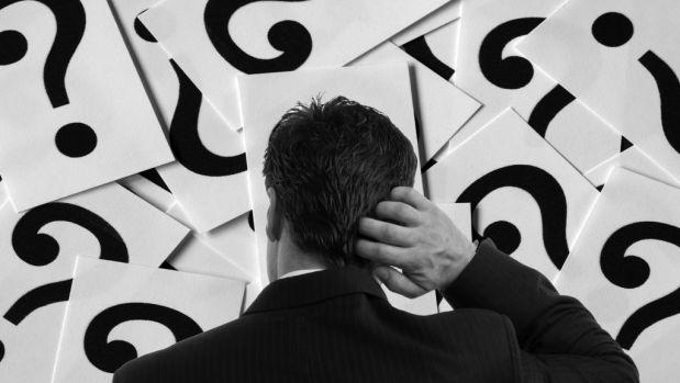 Hombre en blanco y negro rascandose la cabeza mientras mira a una pared llena de interrogaciones negras