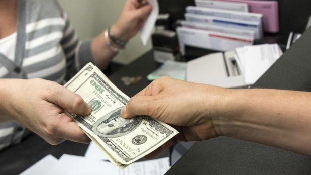 Un banquero dando unos billetes de dinero a una persona detras de un mostrador del banco