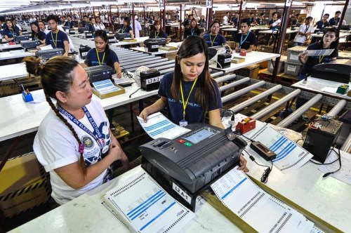 Workers test the function of a vote counting machine (VCM), which will be used for the National Elections on May, at the newly-rented warehouse in Sta. Rosa Laguna on Thursday. (JOHN JEROME GANZON)