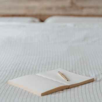empty agenda with pen on crumpled bed in house