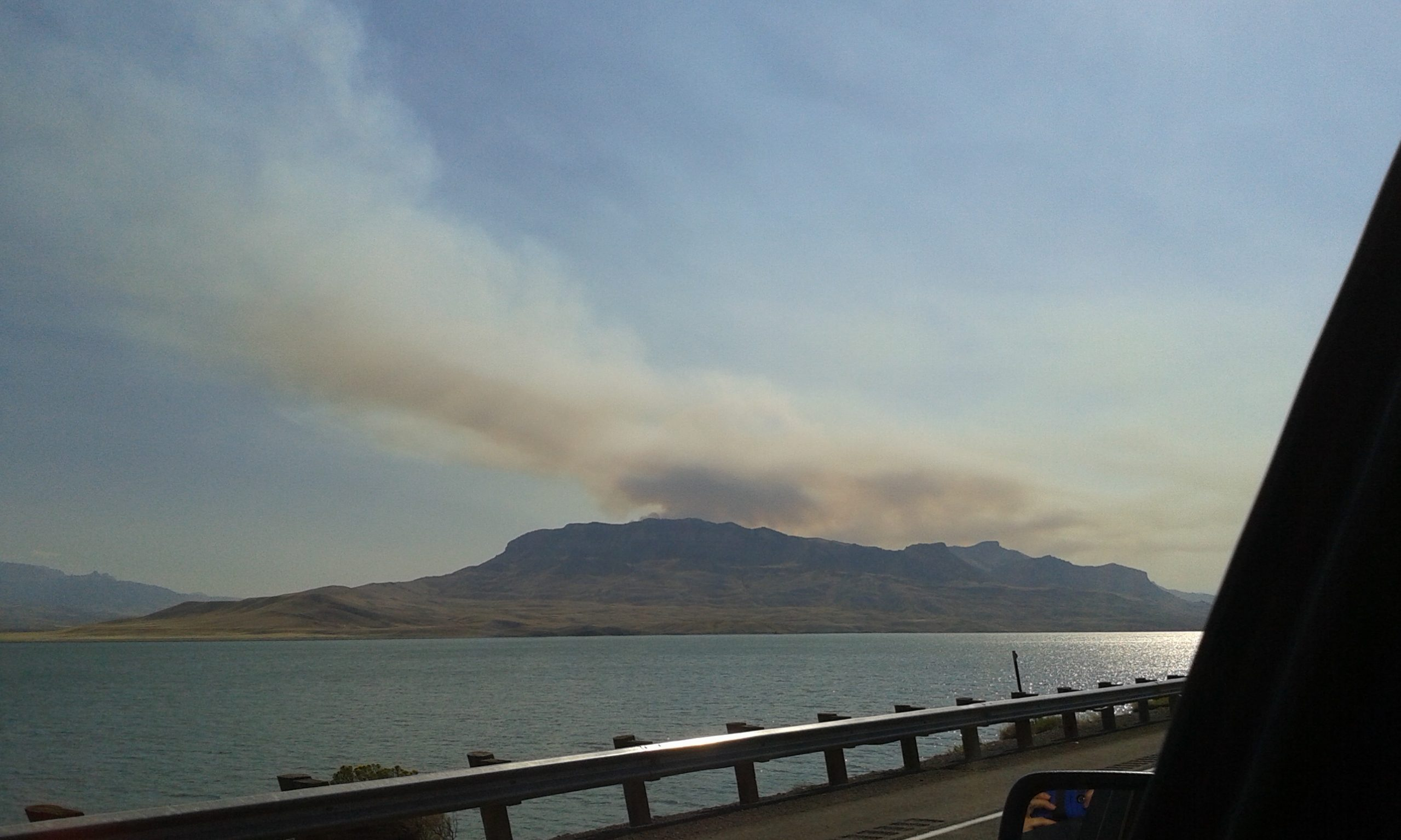 Smoke from the Whit Fire rises over the mountains near the Buffalo Bill Reservoir near Cody, Wyo., as a wildland fire crew from Pennsylvania arrives for their assignment. (Photo by Kimberly Finnigan)