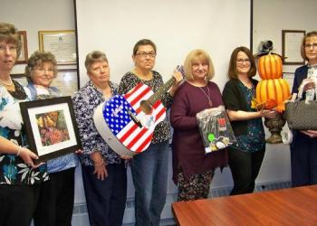 Some of this year's committee members, (from left) Cathie Hugar, Alice Pollack, Jackie Anderson, Kristi Twoey, Ellie Fenton, Ronda Vaughn and Ranea Brewer are showcasing just a few of the items up for bid at this year's 22st annual Anne S. Thacik Charity Auction.  (Provided photo)