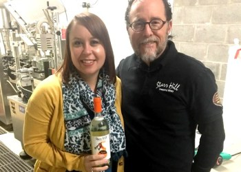 """Marly Doty with Kenn Starr of Starr Hill Winery present a bottle of """"Peeled"""". A portion of the sales of the new wine will support campus programs.  (Provided photo)"""