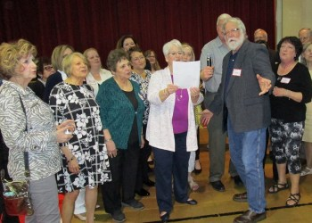 William McNamee, former mayor of Clearfield and member of the class of 1967, leads the singing of the St. Francis School Alma Mater at the alumni reunion held Saturday to celebrate the 125th anniversary of St. Francis School. (Provided photo)