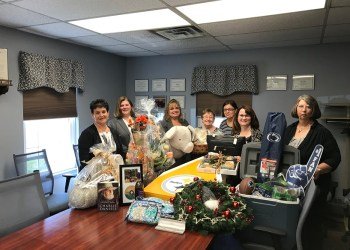 Some of this year's committee members, (from left to right) Michele Fannin, Missy Bishop, Vicky Myers, Joan Bracco, Kristi Twoey, Ronda Vaughn and Cathie Hugar are showcasing just a few of the items up for bid at this year's 24th annual Anne S. Thacik Charity Auction. (Provided photo)