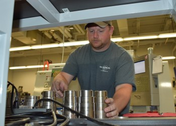 Curt Beck, instructor for introduction to CNC Lathe with some parts created on the lathe in the background.  (Provided photo)