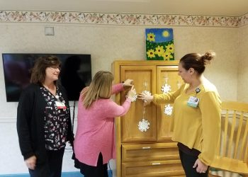 Sharon Goodman, Behavioral Health Inpatient Director, left, hangs snowflakes with staff members at Bright Horizons Inpatient Clinic at Penn Highlands Clearfield. The snowflakes were made as an arts and crafts project by patients of the clinic. The short-term inpatient facility provides a multitude of behavioral health services to patients 55 and older (Photo by Kimberly Finnigan)