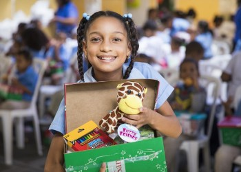 """A girl in the Dominican Republic shows off the """"wow"""" toy she received in her shoebox gift. (Photo courtesy of Samaritan's Purse)"""