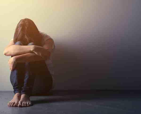 Frau sitzt depressiv auf dem Boden