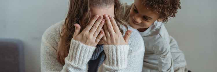 lady covering face with hands while playing with ethnic child