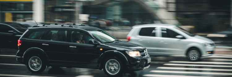 black suv beside grey auv crossing the pedestrian line during daytime