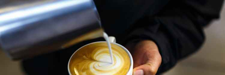 person pouring cream to coffee