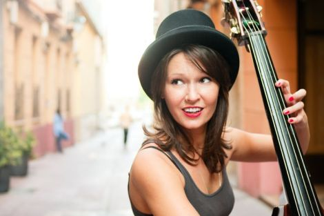 Woman in a hat playing double bass on the street