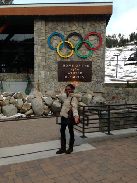 Woman celebrating in front of the Olympics logo at Squaw Valley