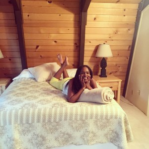 Woman smiling while laying on a bed