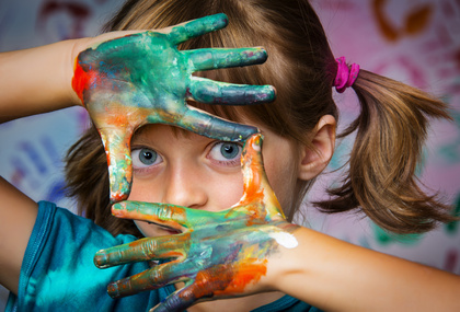 Image of girl with painted hands cradling her face