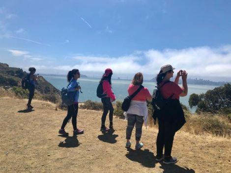 Image of women hiking at Angel Island overlooking the 3 San Francisco bridges