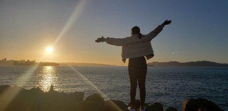 Image of African American Girl looking out into the beautiful sunset over the pacific ocean