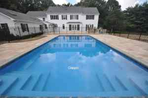 gunite swimming pool with spill-over spa , patio and outdoor kitchen