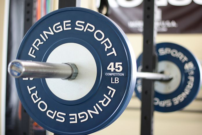 Fringe Sport Competition Bumper Plate Closeup Loaded on Bar Garage Gym Lab