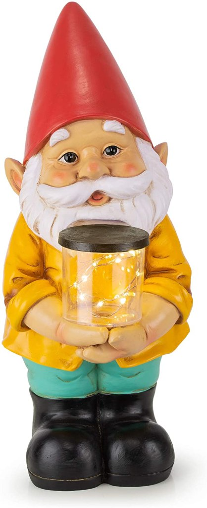 A friendly looking garden gnome with red hat, yellow shirt, holding a jar with fireflies.