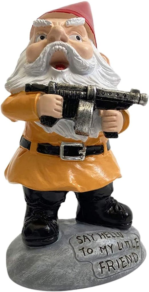 An angry gnome lets out a warcry, mouth wide open, brandishing a submachinegun. He is dressed in tan/orange clothing and shiny black boots.