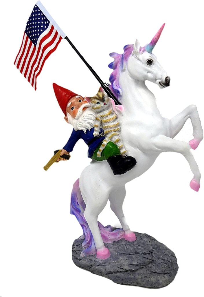 A gnome with red hat rides a white unicorn with a cat in his lap. He is holding a golden .45 caliber handgun and American flag.