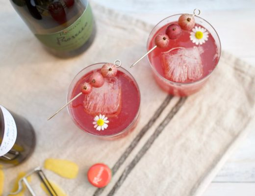 two pink cocktails with gooseberries and chamomile flower