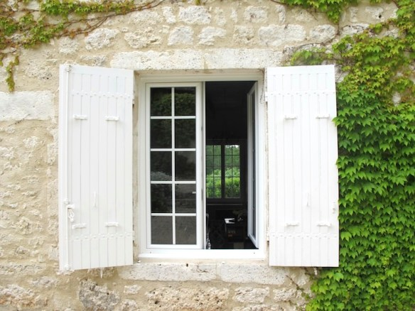 White wooden shutters set into the stone walls