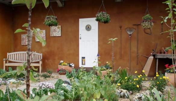 Rusted steel-look paint finish balances the cool greys and whites in the garden. Design Margery Postlethwaite