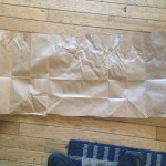 Paper grocery bag with the bottom cut off and cut down the seam