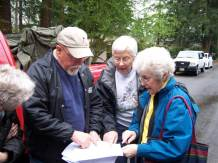 Darrell MacKay, Alta Hansen and Elaine Shreve looking at the map.