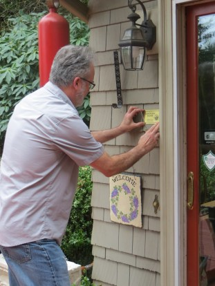 Stan Houseman affixing the Century Home plaque to the Dignan house.
