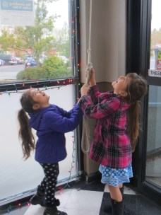 Two girls ringing the bell at the Garden Home Market Place, 2015