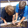 Student preparing garden soil with teacher