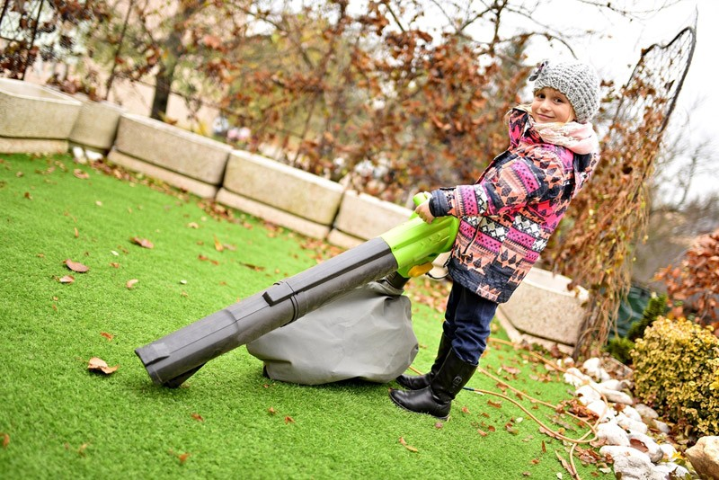 young girl with leaf blower in autumn
