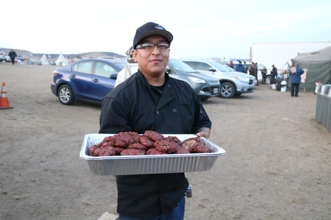 Chef Brian Yazzie with smoked buffalo burgers. Photo by Elizabeth Hoover