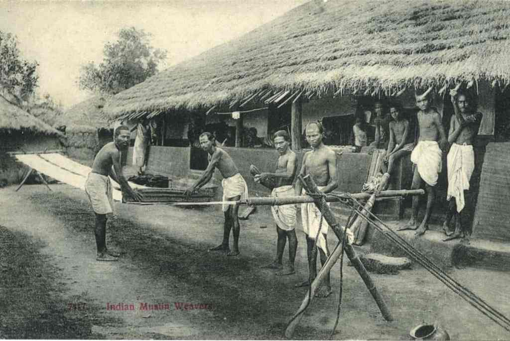 pg 97Indian muslin weavers. Indian muslin weavers, outside their thatched houses, busy with final processing of the fabric.  Reproduction from postcard, Photographer : Unknown