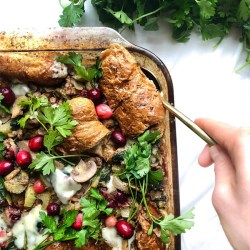tray of stuffing on a white background with a gold spoon in hand