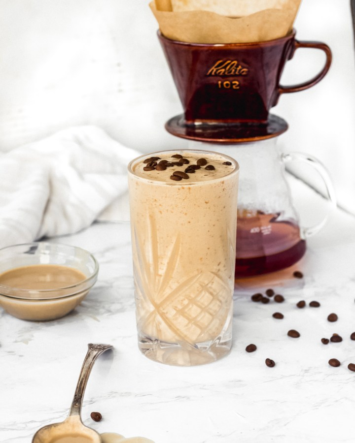 glass with tahini coffee smoothie on marble