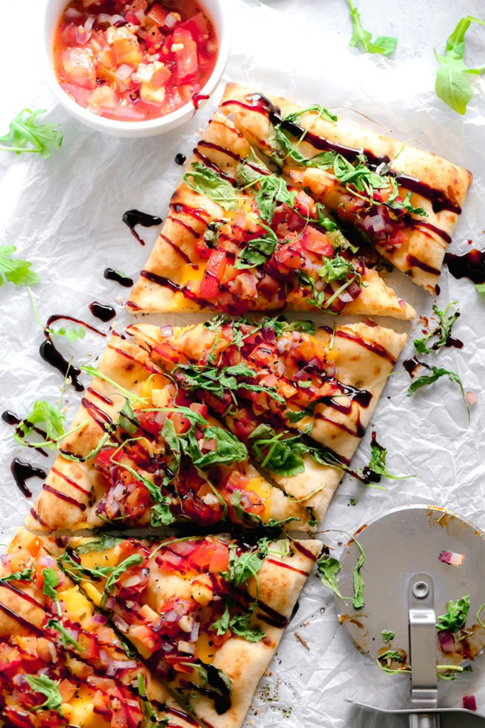 rectangular flatbread with tomatoes and balsamic on a white board