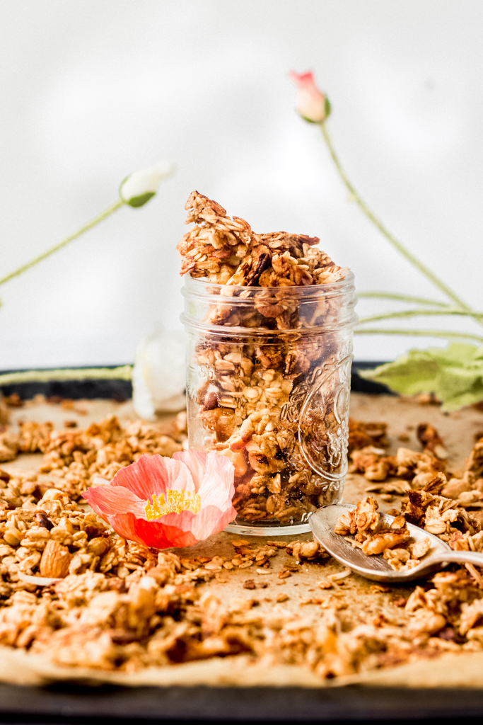clear glass mason jar of granola on a baking sheet with more granola covering it and a pink flower petal