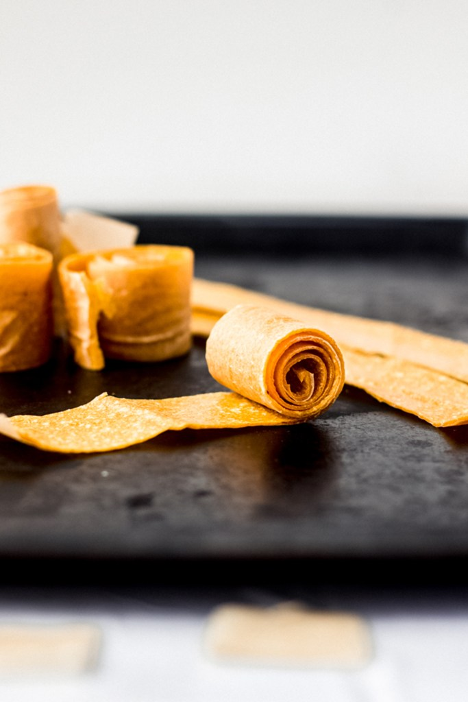 yellow rolled fruit roll up on black sheet tray